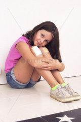 Girl hugging bandaged knees  portrait