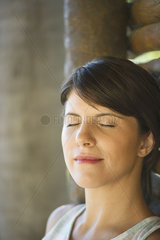 Woman leaning against wall with eyes closed  portrait