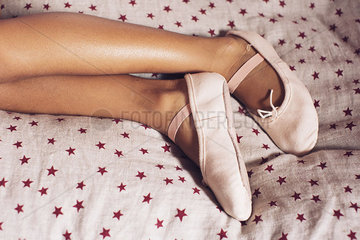 Girl lying on bed  wearing ballet slippers  cropped