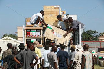 Carrefour  Haiti  lokale Mitarbeiter beim Entladen von Holzkisten