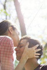 Couple together outdoors  woman kissing man's forehead