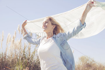 Woman holding up scarf fluttering in wind