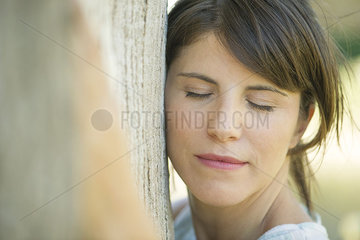 Woman leaning against tree trunk with eyes closed  portrait