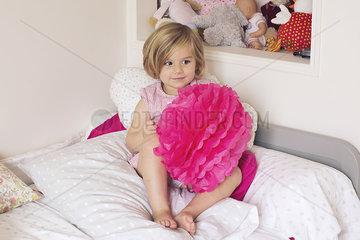 Little girl holding tissue paper pompom