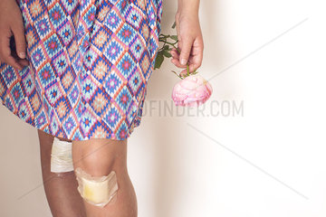 Girl with bandaged knees holding rose  cropped