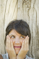 Woman leaning against tree trunk  smiling and holding face in hands  portrait