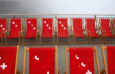 Pilatus Kulm  Schweiz  rote Liegestuehle mit dem Schweizer Kreuz