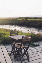 Wooden table and chairs on deck in tranquil scene
