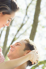 Couple together outdoors  woman stroking man's hair