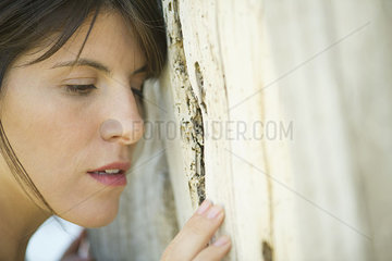 Woman leaning against tree trunk  portrait
