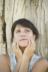 Woman leaning against tree trunk with face in hands  looking up dreamily