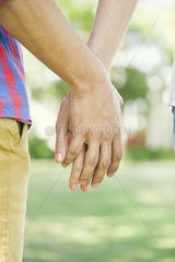 Couple holding hands outdoors  cropped rear view