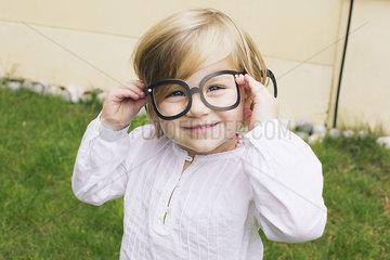 Little girl wearing costume glasses