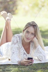 Young woman relaxing in park with smartphone