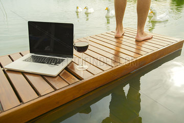 Man standing beside laptop computer and wine glass on lake pier