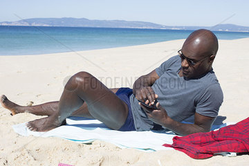 Man lying on beach  using smartphone