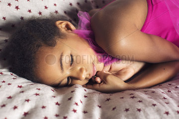 Little girl resting on bed