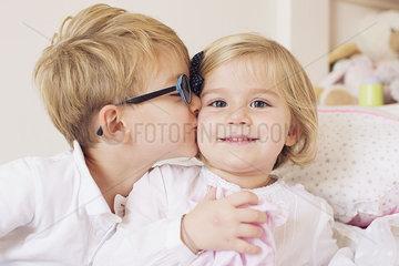 Boy kissing sister's cheek