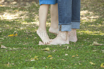 Boy standing barefoot and tiptoes on father's feet