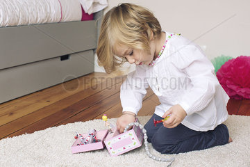Little girl removing necklace from jewellery box