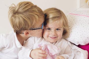 Boy kissing little sister's cheek