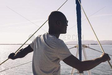 Man on sail boat  looking at view