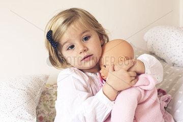 Little girl hugging doll