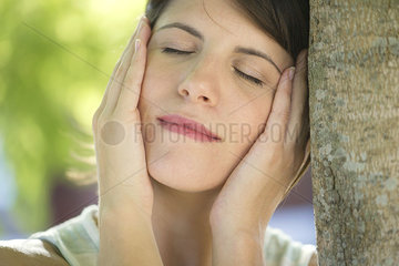 Woman leaning against tree trunk with hands on cheeks  eyes closed