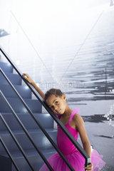 Little girl in ballerina costume leaning against staircase railing