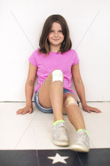 Girl sitting on floor with both knees bandaged  smiling