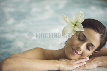Woman in pool  resting head on arms