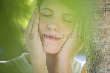Woman leanng against tree trunk with hands on cheecks  eyes closed
