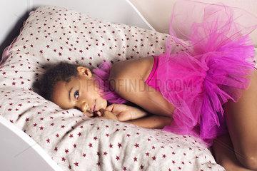 Girl lying on bed in tutu