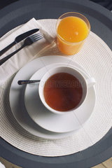 Cup of hot tea and glass of orange juice