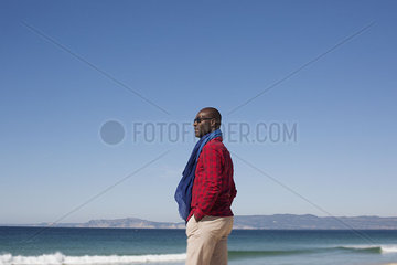 Man standing alone on beach  looking at view