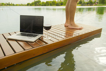 Man standing beside laptop computer and glass of wine on pier
