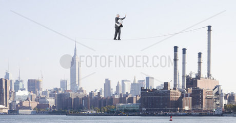 Oversized businessman walking on tightrope above city  carrying briefcase stuffed with cash