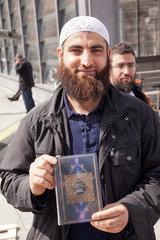 Berlin  Deutschland  Mann zeigt den Koran