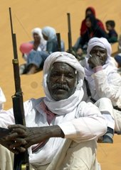 Africa  Algeria  Saoura area  Sahara desert  hunters sitting on sand hill