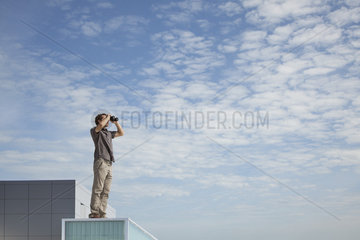 Oversized man standing on rooftop  looking through binoculars