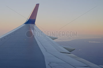 View of airplane wing over coast of Iceland