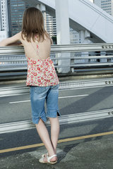 Girl leaning against railing on side of road