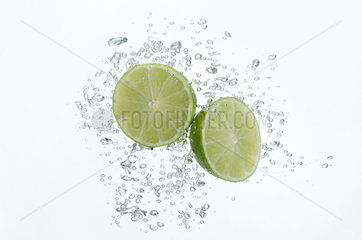 Lime halves submerged in sparkling water