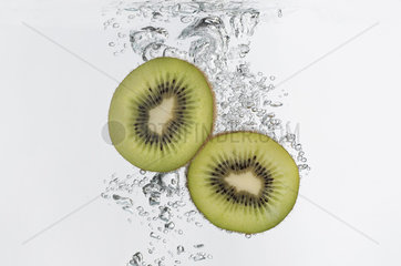 Kiwi halves submerged in water
