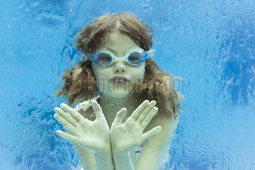 Girl wearing goggles swimming underwater in swimming pool