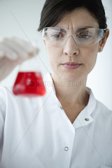 Scientist holding conical flask containing red liquid
