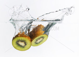 Kiwi halves splashing into water