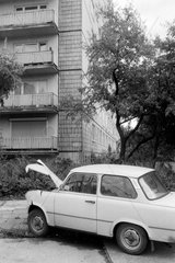 Berlin  Deutschland  zerstoerter Trabant parkt vor einem Plattenbau
