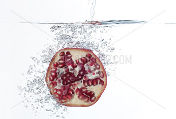 Pomegranate half submerged in water