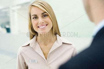 Woman wearing nametag smiling at camera